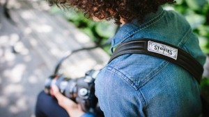 Black leather camera strap from ONA slung over woman's shoulder