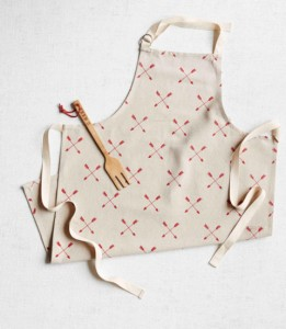 White apron with design and wooden fork on it