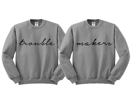 "matching sweaters, one says ""trouble"" the other says ""makers"""
