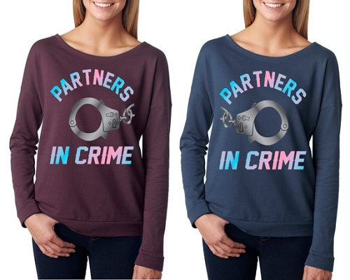 "Matching sweaters say ""Partners in crime"" with pair of handcuffs."